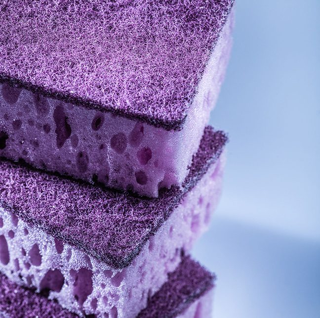 New violet washing sponges on white surface.