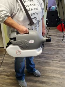 care cleaning staff member with Disinfecting fogger machine